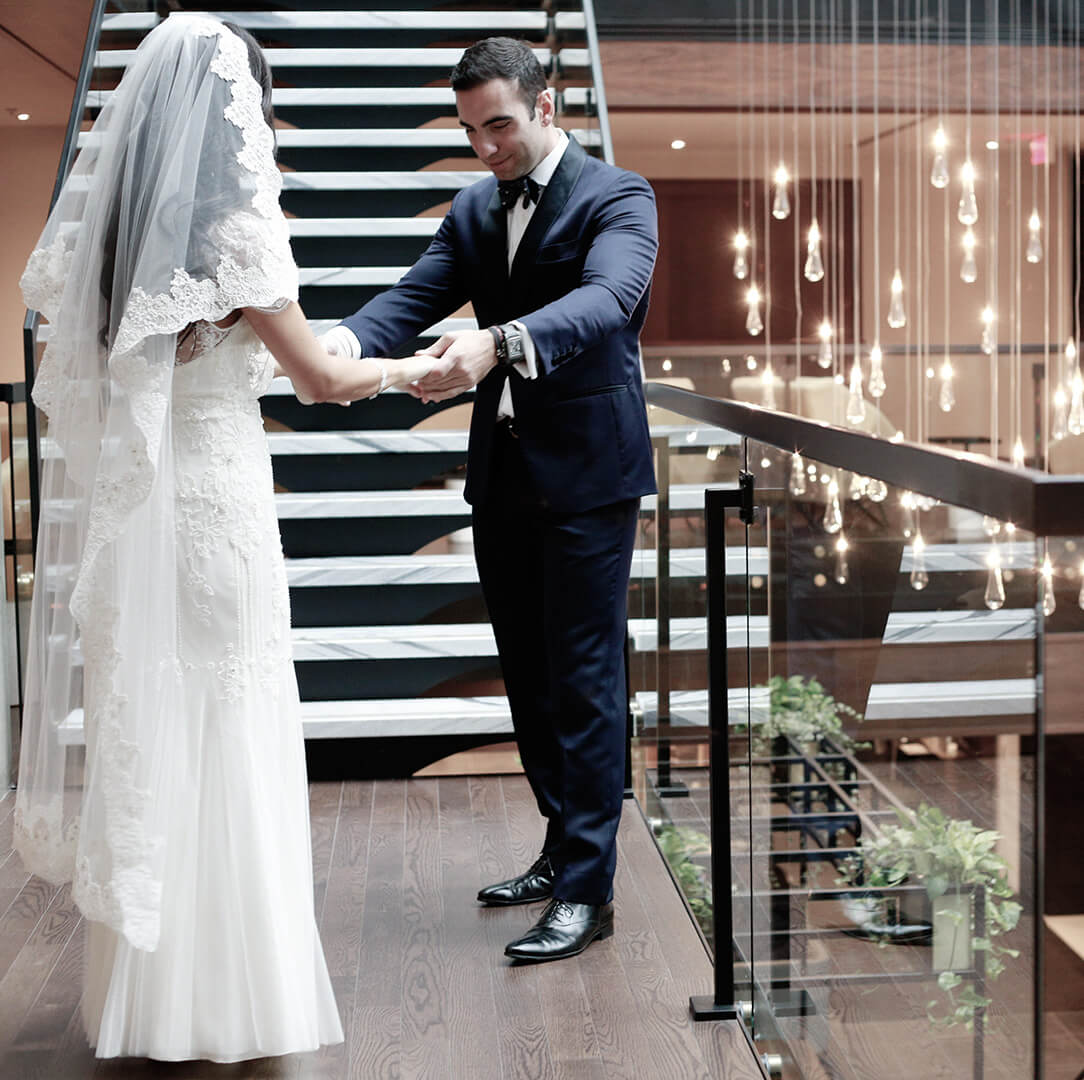 A bride and groom hold hands on a stairwell in the atrium of the Hotel William Gray