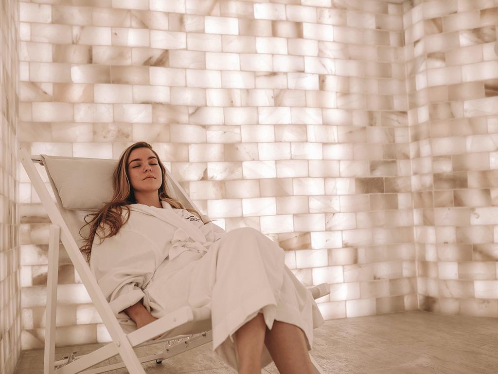 Une femme qui se relaxe sur une chaise dans une salle de sel himalayen