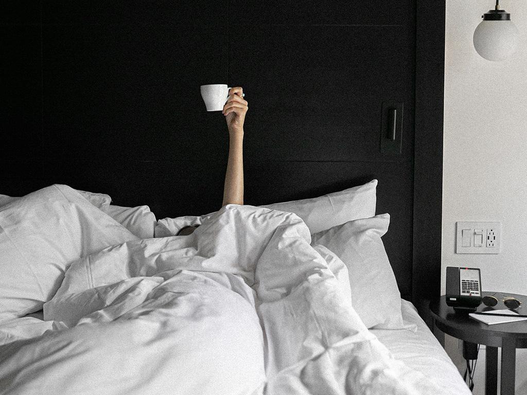 Une fille dans un lit qui tient une tasse de café à la main