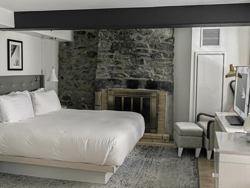 Chambre avec un lit,un fauteuil, une cheminée et un mur de pierres