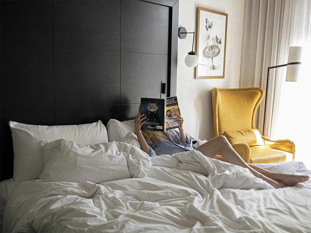 A woman laying down on one of the beds of the Hôtel William Gray and reading a magazine.