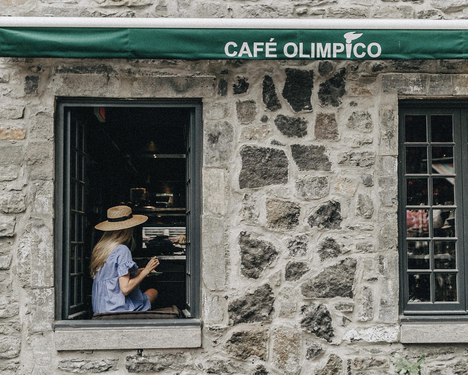 Une femme à la fenêtre du Café Olimpico en train de boire un café
