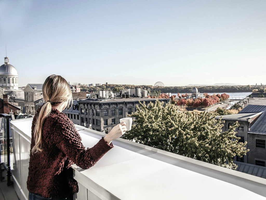 A girl with a cup of coffee in her hand enjoying the Old Montreal view