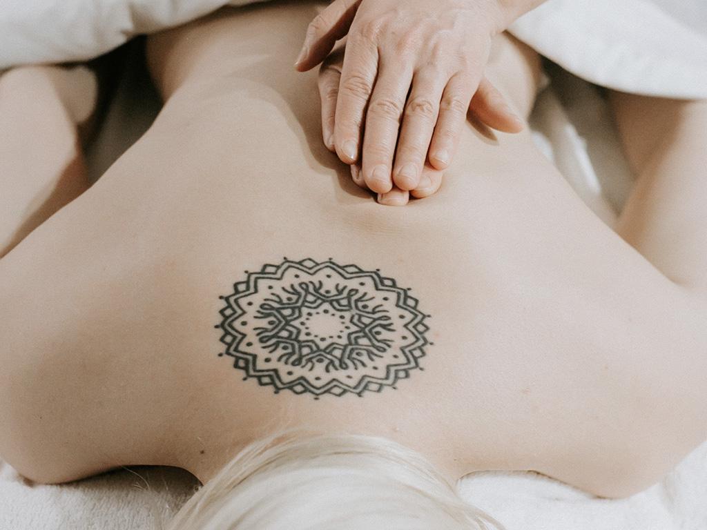 Une fille avec un tatouage dans le dos en train de se faire masser